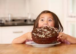 little-girl-about-to-chomp-down-on-big-chocolate-cake-with-a-funny-expression-on-her-face